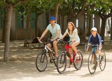 Familia feliz de tres que completan un ciclo en el camino de la calle Foto de archivo