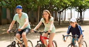 Familia feliz de tres que completan un ciclo en la calle Imagen de archivo