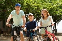 Familia feliz de tres que completan un ciclo a través de ciudad Imágenes de archivo libres de regalías