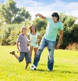 Familia feliz de tres que juegan con la bola Foto de archivo libre de regalías