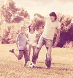 Familia feliz de tres que juegan con la bola Fotos de archivo libres de regalías