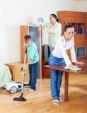 Familia feliz de tres que limpian en hogar Foto de archivo