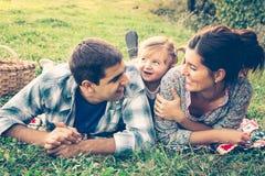 Familia feliz de tres que mienten en la hierba en otoño Fotos de archivo