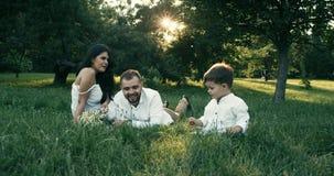 Familia feliz de tres que mienten en la hierba en parque del verano Juegan y sonríen 4K Cámara lenta almacen de video