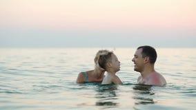 Familia feliz de tres que se bañan en el mar almacen de video