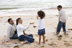 Familia feliz del African-American que juega en la playa Foto de archivo libre de regalías