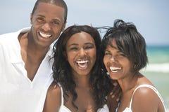 Familia feliz del afroamericano en la playa Foto de archivo