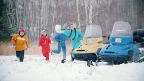 Familia feliz del bosque del invierno en la ropa colorida que juega bolas de nieve cerca de las motos de nieve funcionamiento a l almacen de video