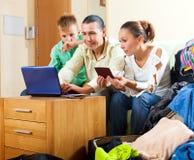 Familia feliz del hotel de reserva tres en Internet usando lapt Fotografía de archivo