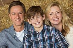 Familia feliz del niño del muchacho de la mujer del hombre en Hay Bales Fotografía de archivo