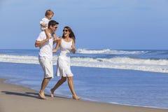Familia feliz del niño de la mujer del hombre que juega en la playa Foto de archivo libre de regalías