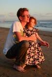 Familia feliz del pelirrojo en la playa de la puesta del sol fotografía de archivo