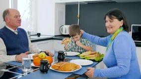 Familia feliz del pensionista que come los bollos durante almuerzo metrajes