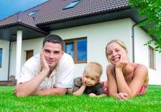 Familia feliz delante de la casa Fotos de archivo libres de regalías