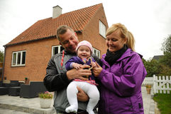 Familia feliz delante de la casa Imagenes de archivo