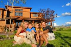Familia feliz delante de la casa Foto de archivo libre de regalías