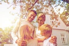 Familia feliz delante de la casa al aire libre imagen de archivo libre de regalías