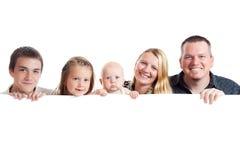 Familia feliz detrás de la tarjeta blanca Foto de archivo libre de regalías