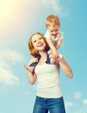 Familia feliz. el bebé se sienta a horcajadas en los hombros de la madre y Fotografía de archivo