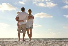 Familia feliz el las vacaciones de la playa que miran el océano imagen de archivo libre de regalías