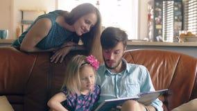Familia feliz el padre joven y su pequeña hija rubia están leyendo una historia en el sofá de cuero en el comedor 4K almacen de metraje de vídeo