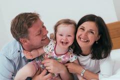 Familia feliz en cama Foto de archivo