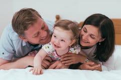 Familia feliz en cama Fotos de archivo
