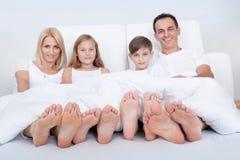 Familia feliz en cama bajo cubierta que muestra pies Foto de archivo