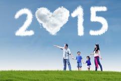 Familia feliz en campo debajo de la nube de 2015 Fotografía de archivo