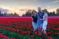 Familia feliz en campos del tulipán en la puesta del sol Imágenes de archivo libres de regalías