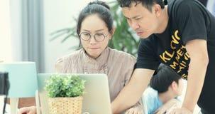 Familia feliz en casa usando un ordenador portátil que hace compras en línea Y niño asiático joven que juega la tableta en fondo almacen de metraje de vídeo