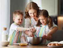 Familia feliz en cocina la madre y los ni?os que preparan la pasta, cuecen las galletas imagen de archivo libre de regalías