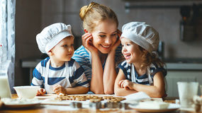 Familia feliz en cocina madre y niños que preparan la pasta, vagos foto de archivo
