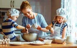 Familia feliz en cocina madre y niños que preparan la pasta, vagos