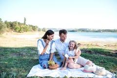 Familia feliz en comida campestre cerca del lago imagen de archivo libre de regalías