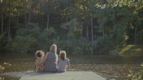 Familia feliz en el abrazo del amor que descansa sobre el embarcadero por el lago almacen de video