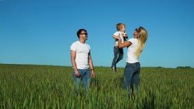Familia feliz en el campo en un día soleado en el parque que se divierte y que pasa el tiempo junto El hijo se sienta en su ` s d almacen de metraje de vídeo