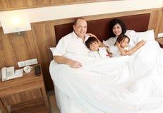 Familia feliz en el dormitorio Foto de archivo libre de regalías