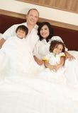 Familia feliz en el dormitorio Foto de archivo