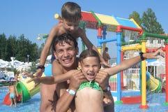 Familia feliz en el parque del agua Fotos de archivo