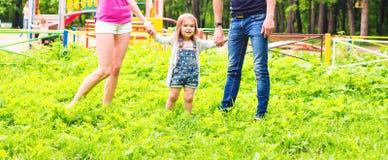 Familia feliz en el parque Paseo feliz de la mamá, del papá y del bebé El concepto de una familia feliz Los padres llevan a cabo  imágenes de archivo libres de regalías