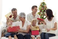 Familia feliz en el país que abre regalos de Navidad Fotos de archivo libres de regalías