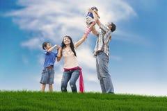Familia feliz en el prado fotografía de archivo