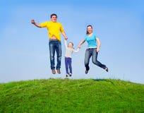 Familia feliz en el salto Foto de archivo libre de regalías
