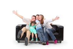 Familia feliz en el sofá de cuero negro Imágenes de archivo libres de regalías