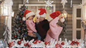 Familia feliz en el sombrero de los jerséis que abraza en el pórtico de la Navidad Árbol del Año Nuevo almacen de video
