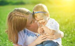 Familia feliz en hija y risa del bebé de las cosquillas de la madre de la naturaleza Imagenes de archivo