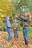 Familia feliz en juego del bosque del otoño con la hoja caida Imagen de archivo libre de regalías