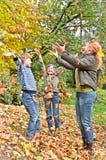 Familia feliz en juego del bosque del otoño con la hoja caida Imágenes de archivo libres de regalías