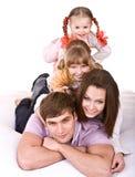 Familia feliz en la cama blanca. Foto de archivo
